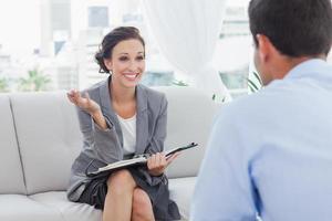 lächelnde Geschäftsfrau im Gespräch mit ihrem Kollegen foto
