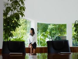 Geschäftsfrau, die aus dem Fenster im Besprechungsraum nachdenkt foto
