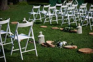 Reihen weißer Stühle arrangiert für eine Hochzeitszeremonie foto