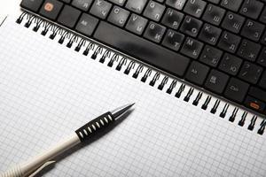 Stift auf einem Notizbuch in eine Zelle und Tastatur foto