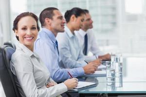 Geschäftsfrau lächelt in die Kamera, während ihre Kollegen t hören