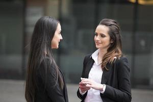 Zwei Geschäftsfrauen stehen draußen und reden. foto