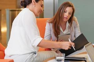 multiethnische schöne Geschäftsfrauen, die in der Geschäftslobby arbeiten foto