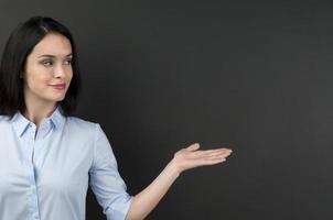 Frau präsentiert etwas auf einer Tafel foto