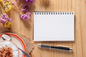 Notizbuch mit Stift auf Holztisch foto