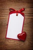 Adresskarte mit Bogen und Herz auf altem hölzernen Hintergrund. foto