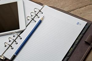 Tagebuch mit digitalem Tablet-PC auf einem Holztisch foto