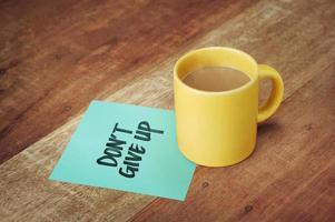Papier mit Handschrift und Kaffeetasse auf Holztisch