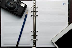 Tagebuch und Retro-Kamera mit digitalem Tablet-PC foto
