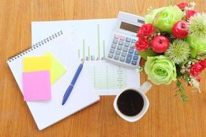 Diagramm und Taschenrechner auf Holztisch mit Kaffee foto