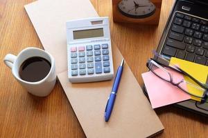 Notizbuch und Laptop auf Holztisch mit Kaffee foto