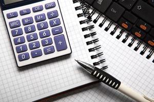 Stift mit Taschenrechner auf einem Notebook und Tastatur foto