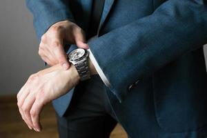 das Foto des Geschäftsmannes in einem Anzug. eine Hand mit Stunden