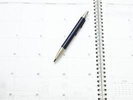 Kalenderseite im Organizer und ein Stift als Hintergrund foto