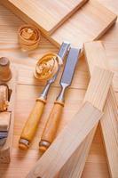 Tischlermeißel und Flugzeug auf Holzbrettern