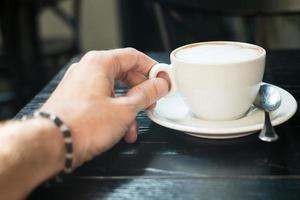 Hand hält eine Tasse Cappuccino