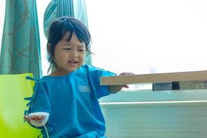 Krankheit asiatische Kinder sitzen auf einem Stuhl im Krankenhaus foto