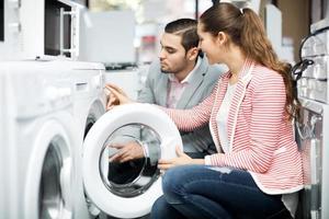 glückliches Familienpaar, das neue Waschmaschine kauft foto