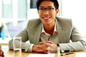 glücklicher asiatischer Mann, der am Tisch sitzt foto