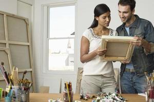 Paar, das Leinwände im Künstleratelier betrachtet foto