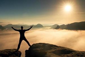 lustiger springender Wanderer feiern Triumph. bleib zwischen zwei Gipfeln foto