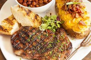Steak mit Ofenkartoffel, Pinquitobohnen und gegrilltem Knoblauchbrot foto