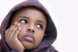 Nahaufnahmeporträt des Jungen, der seinen Kopf auf seiner Hand ruht foto