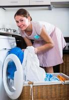 Hausfrau mit Wäschekorb in der Nähe von Waschmaschine drinnen