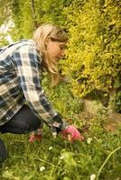 Das blonde Mädchen im Profil kümmert sich um die Hecke seines Gartens foto