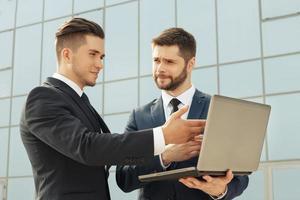 Geschäftsleute, die Laptop während einer Besprechung verwenden foto