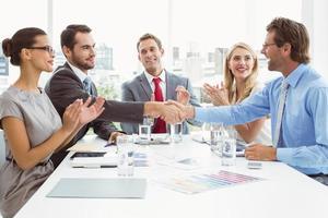 Führungskräfte, die sich im Sitzungssaal die Hand geben foto