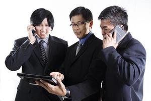 Treffen mit drei Geschäftsleuten und Verwendung eines Mobiltelefons
