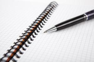Stift auf einem Notizbuch in eine Zelle foto