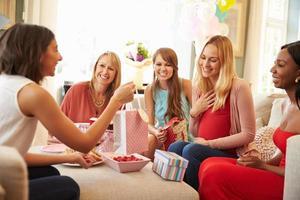 Gruppe von Freundinnen treffen sich zur Babyparty zu Hause foto