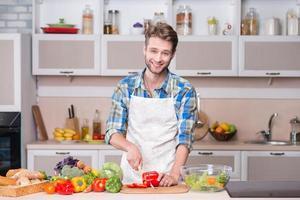junger lächelnder Mann, der Abendessen in der Küche kocht foto