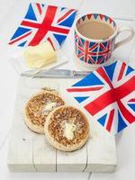 gebutterte englische Fladen mit einer Tasse Tee und Fahnen foto