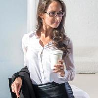 Frau in Gläsern mit der Tasse Kaffee oder Tee foto