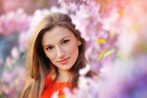 Porträt der hübschen Frau nahe dem blühenden Baum im Park. foto
