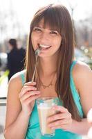 lächelnde junge Frau, die Latte Macchiato im türkisfarbenen Trägershirt trinkt foto