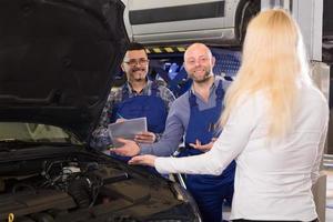 Mechaniker erklären dem Besitzer das Autoproblem foto