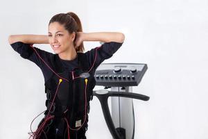 junge fit Frau Übung auf Elektro-Muskelstimulationsmaschine