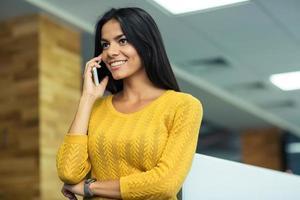 glückliche Geschäftsfrau, die am Telefon spricht foto