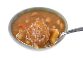 Fleischbällchen und Kartoffeln auf einem Löffel mit Mahlzeit im Hintergrund