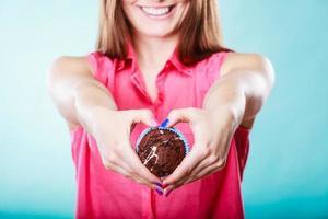 Hände Herzform mit Muffin. Süßwaren.