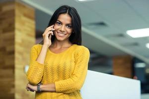 lächelnde Geschäftsfrau, die am Telefon spricht foto