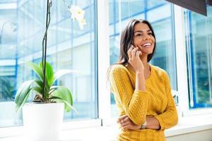 Geschäftsfrau, die auf Smartphone im Büro spricht foto