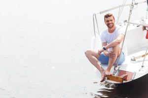 angenehmer Mann, der auf dem Yachtdeck sitzt