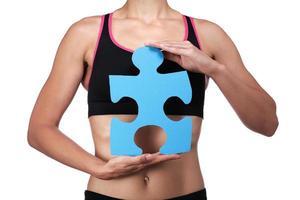 Sporttrainer hält ein Puzzleteil