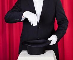 Zauberer in einem schwarzen Anzug foto