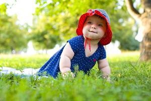 Porträt des lustigen kleinen Mädchens auf dem Rasen foto